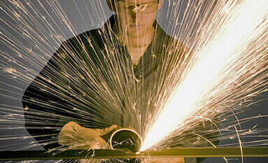 A shower of sparks being emitted during a grinding and deburring application. A welder in protective gear, looking down at the welding application.