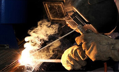 Welding smoke rising from a welding application being performed by a machine operator in a welding mask.