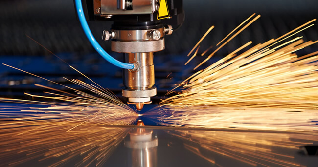 Golden sparks are being emitted from a laser and plasma cutting tool in motion.