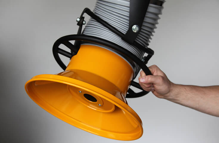 A machine operator holding onto the hood of a fume arm. An emphasis on the metal hood which offers 2x the suction distance when compared to competitors.