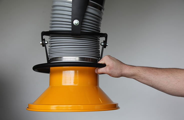A machine operator holding onto a fume extractor arm. An emphasis on the effortless 360° rotation and 14-inch metal hood.