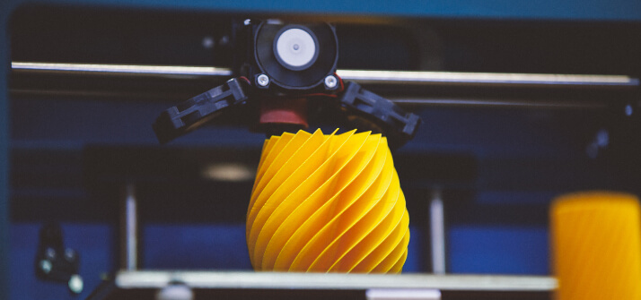 A 3D printer in the process of printing a yellow product.