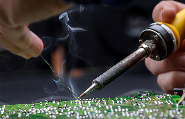 Smoke from a soldering work piece is rising up toward the machine operator. A welder holds a solder tool in one hand and a piece of metal in the other.
