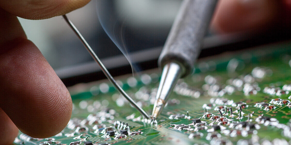 A close up of a machine operator's hands soldering an electronic component. Soldering smoke is rising up towards the machine operator.