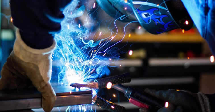 Smoke and sparks are being transmitted during a welding application. A welder in a protective mask is holding the workpiece with one hand and welding with the other.